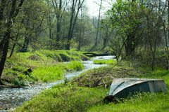 Woods. Upturned boat on the bank of a river in the forest Stock Photos