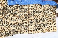 WOODSHED με τα κομμάτια του ξύλου συσσώρευσε επάνω για το χειμώνα και το χιόνι στοκ εικόνες με δικαίωμα ελεύθερης χρήσης
