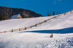 Woodshed above the snowy hillside with fence. Woodshed above the snowy hillside with wooden fence. lovely mountainous rural scenery Stock Image