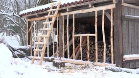 Woodshed with firewood pile and ladder at snowy winter time. 4K. Handmade wooden woodshed with firewood pile and ladder at snowy winter time. 4K stock footage
