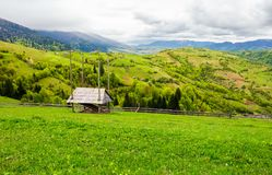 Woodshed on grassy hill in rural area. Beautiful springtime countryside landscape Stock Image