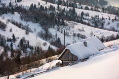 Woodshed on hillside in deep snow. Beautiful winter rural scenery in the mountainous village outskirts at sunrise Stock Photos