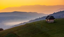 Woodshed on a hillside at sunrise. Beautiful countryside scenery of mountainous area. yellow sky over the purple mountains. fog down the valley of Synevir Royalty Free Stock Images