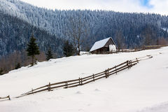 Woodshed on the hillside in winter mountains Royalty Free Stock Photo