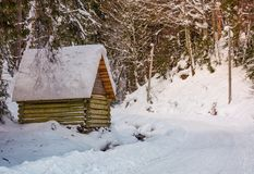 Woodshed by the road in winter forest. Lovely nature scenery Stock Photos