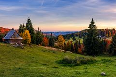 Woodshed and trees on hillside meadow at sunset. Mountainous village among mixed forest with colorful foliage. splendid rural landscape of Romania Stock Image