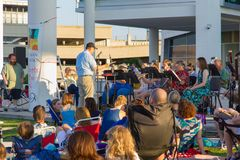 A woodwind ensemble performs on a warm June evening. AUSTIN, TEXAS - JUNE 1 2014: musicians and their conductor performing out of doors in bright sunlight royalty free stock image