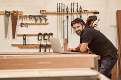 Woodwork artisan in his workshop studio with a laptop Royalty Free Stock Photos