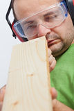Woodwork - checking linearity. Woodwork - man checking linearity of wooden planck - closeup stock image