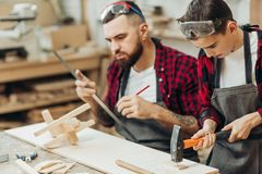 Woodwork classes for children and creativity concept. In carpentry coworking studio children and youngsters can learn a useful profession together with Dad royalty free stock image