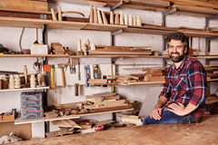 Woodwork craftsman in studio with shelves of wood pieces. Portrait of a craftsman smiling at the camera while sitting on the edge of his workbench, in his Stock Photography