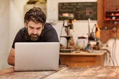 Woodwork designer with a beard in his workshop using laptop Royalty Free Stock Image