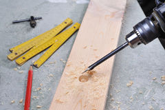 Woodwork. Drilling in wood. Woodwork in the workshop. Carpenter working with wood royalty free stock photography