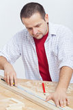 Woodwork - man measuring wooden planck Royalty Free Stock Images