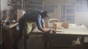 Woodwork man in shirt planes a tree in a dark authentic workshop. Slow mo stock video footage