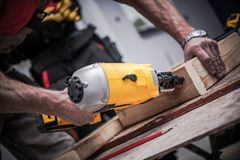 Woodwork Using Nail Gun. Caucasian Construction Worker Creating Wood Elements Using Powerful Nail Gun Tool royalty free stock photo