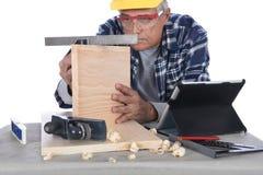 Woodworker που ελέγχει το επίπεδο Στοκ εικόνα με δικαίωμα ελεύθερης χρήσης