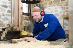 Woodworker τέμνουσα σανίδα στο δύναμη-πριόνι Στοκ εικόνες με δικαίωμα ελεύθερης χρήσης