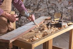 Woodworker используя зубило для того чтобы приглаживать вниз с древесины стоковая фотография