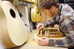 Woodworker budynku gitara w warsztacie Fotografia Stock