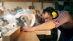 Woodworker with a circular saw is processing wood in slow motion. HD stock video footage