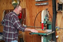 A woodworker cutting a board. With a bandsaw in his workshop royalty free stock images