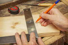 Woodworker draws a line on a wooden board Royalty Free Stock Image