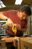 Woodworker with Drill. Vertical image of a woodworker using an electric drill on a board held in a vise Stock Photo