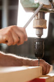 Woodworker drilling a plank with machinery Stock Photography