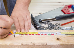 Woodworker hands and carpentry tools. Close-up image with a carpenter measuring a plank of wood and a bunch of woodworking tools in the background stock photo