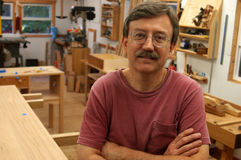 Woodworker in His Shop. Woodworker facing the camera with his shop in the background Royalty Free Stock Photos
