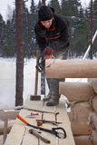 Woodworker makes groove at end logs using chainsaws. Royalty Free Stock Photography