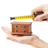 Woodworker measuring chest of drawers with a tape measure. Carpentry concept Royalty Free Stock Photography