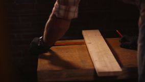 Woodworker is measuring distance and making mark on a wooden detail stock footage