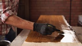 Woodworker is painting wood by brown color in small craft workshop stock footage