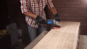 Joiner is sanding a board for furniture production stock footage
