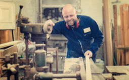 Woodworker processing planks of wood Stock Photography