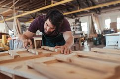 Woodworker skillfully sanding pieces of wood in his workshop Royalty Free Stock Image
