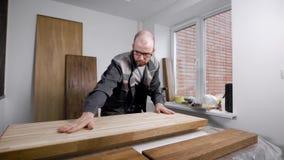Woodworker stawia szalunek deskę na stole w warsztacie mała ciesielka, przygotowywa dla przetwarzać zdjęcie wideo