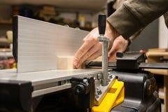 Craftsman straitening wood on a jointer stock photos