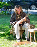 Woodworker is twining making souvenirs from the tat withe. Royalty Free Stock Image