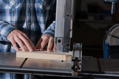 Woodworker uses the band saw to cut a piece of wood to size stock photos