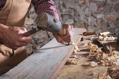 Woodworker using chisel to smooth down wood. Adult male woodworker wearing plaid shirt and overalls using chisel and mallet to smooth down wood beam royalty free stock photo
