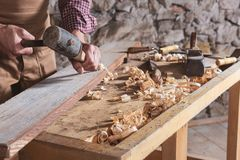 Woodworker using chisel to smooth down wood. Adult male woodworker wearing plaid shirt and overalls using chisel and mallet to smooth down wood beam royalty free stock photos