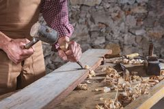 Woodworker using chisel to smooth down wood. Adult male woodworker wearing plaid shirt and overalls using chisel and mallet to smooth down wood beam stock image