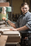 Woodworker using drilling machine Royalty Free Stock Images