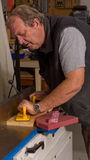 Woodworker using a jointing machine. To flatten a length of wood in a recommended safe manner Stock Photos