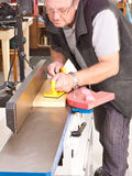 Woodworker using a jointing machine. To flatten a length of wood in a recommended safe manner Royalty Free Stock Image