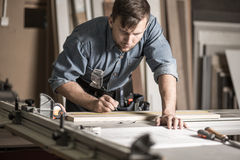 Woodworker working on professional workbench. Picture of handsome woodworker working on professional solid workbench Stock Photos