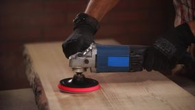 Polishing machine is in hands of experienced master of wood processing stock footage